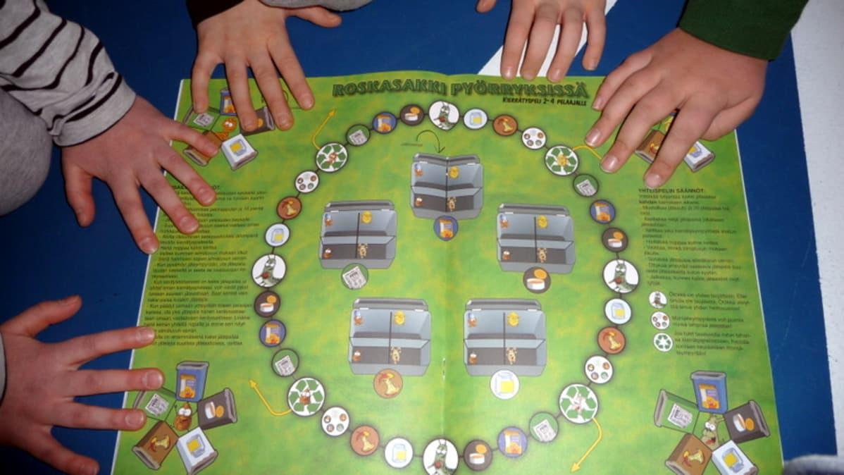 Lasten käsiä on lautapelin ympärillä.