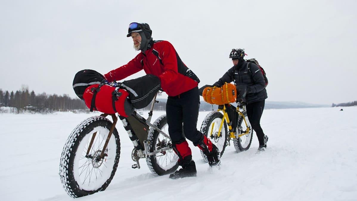 Miehet taluttavat maastopyöriä jäällä