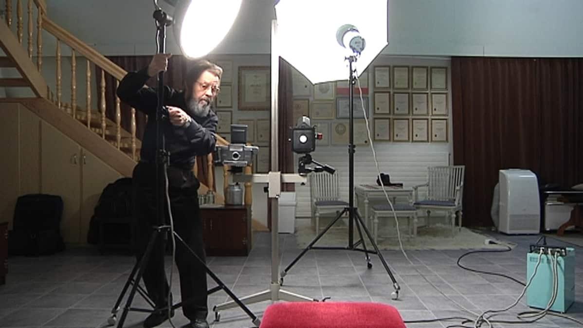 Kalervo Puskala siirtää lamppuja studiossa.