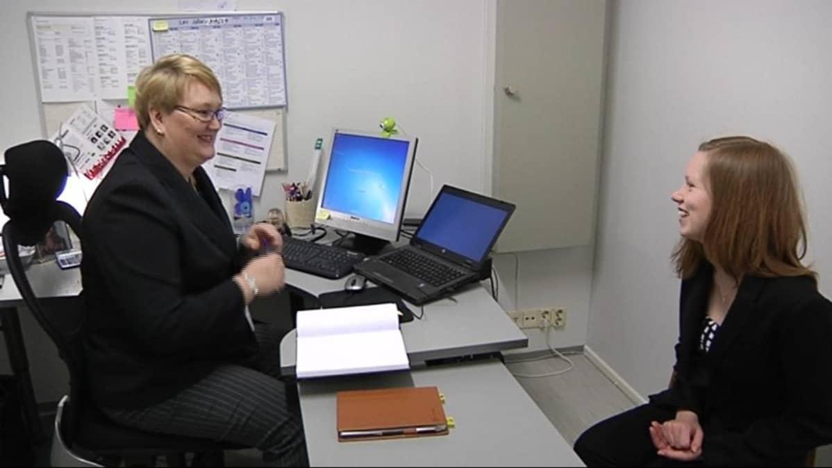 Kaksi naista istuu toimistossa.