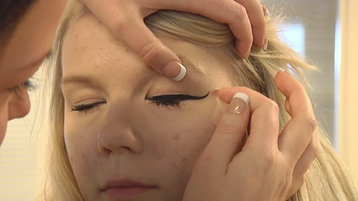 Nuorelle naiselle laitetetaan silmänrajaustarroja.