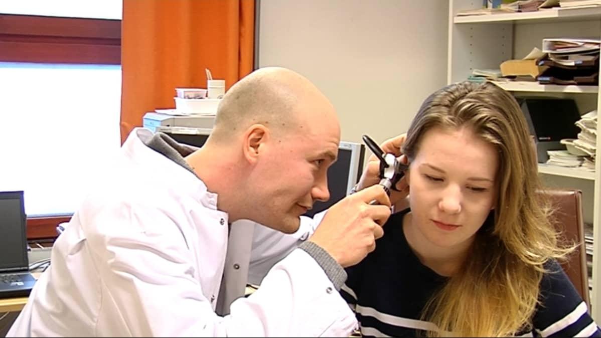 Lääkäri Juuso Rajala tutkii potilaan korvaa.