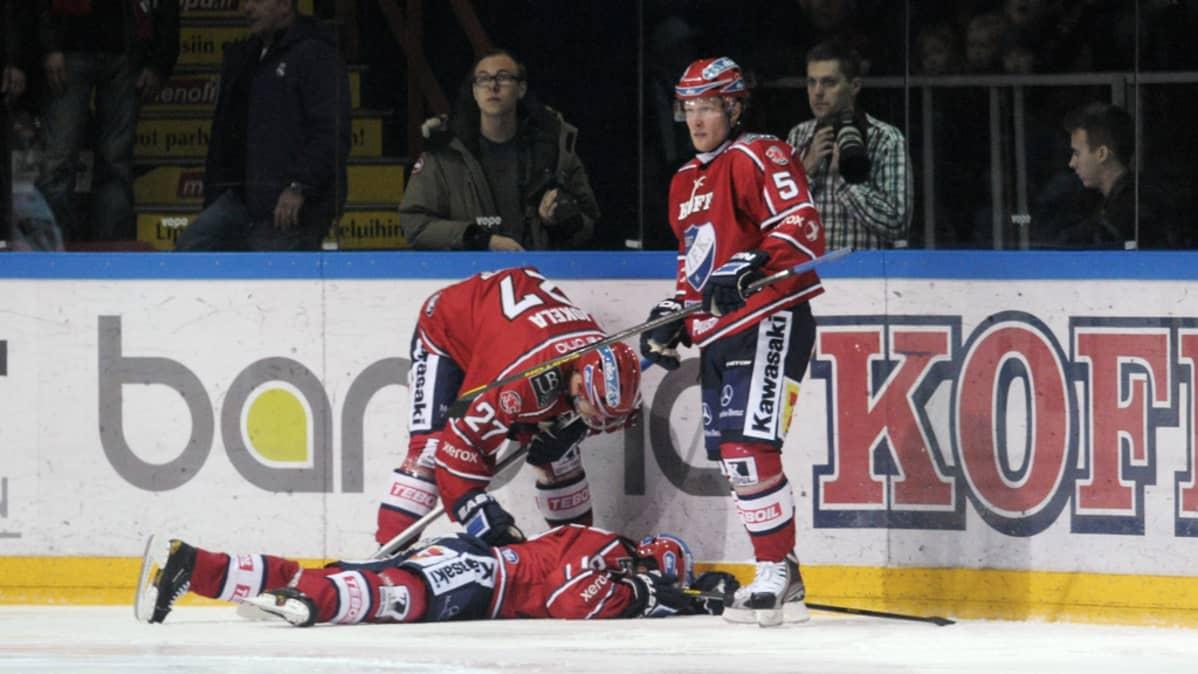 Ville Peltonen makaa jäässä taklauksen jälkeen.