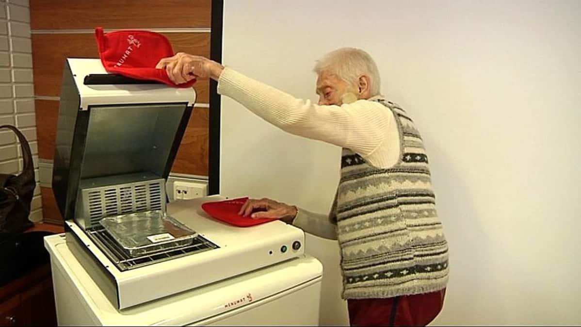 Pirkko Romppanen lämmittää ruokaa ateria-automaatilla.