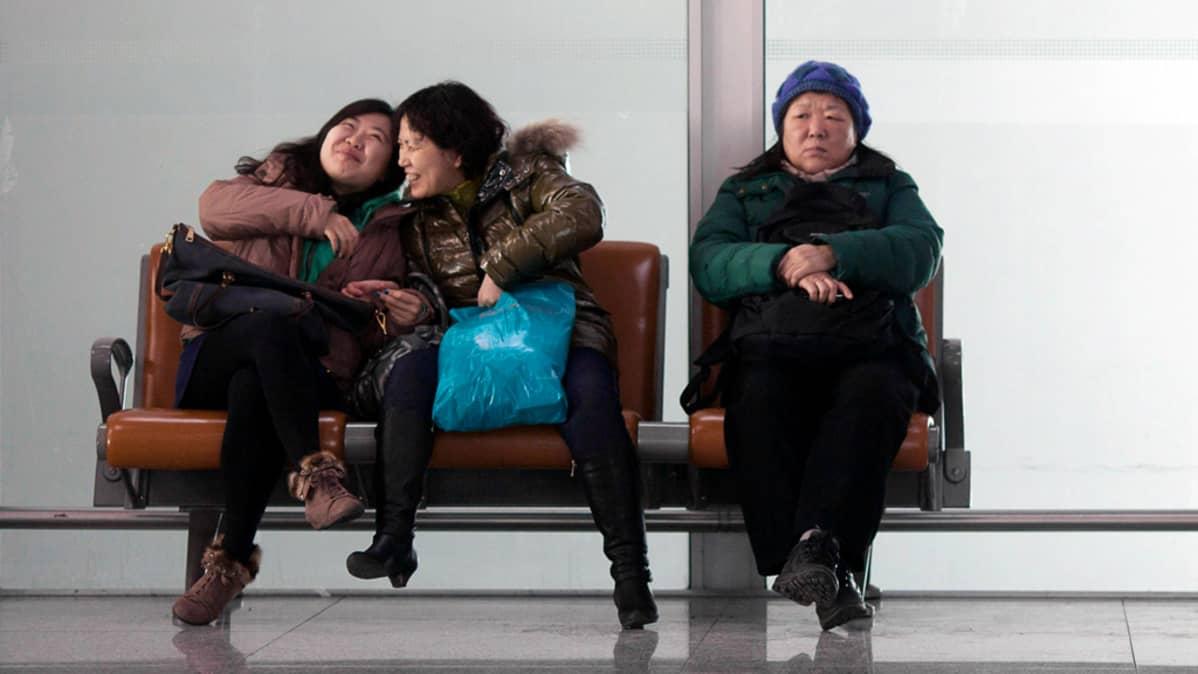 Kaksi naista nauraa vakavan naisen vieressä.