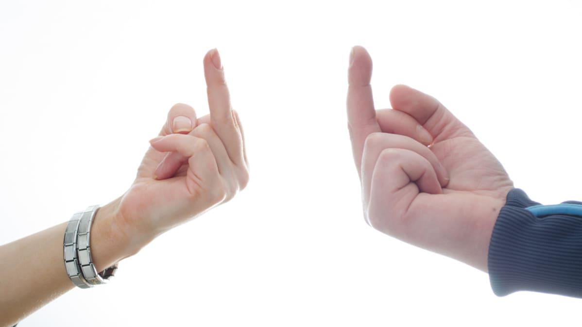 Naisen ja miehen kädet näyttävät toisilleen keskisormea valkoista taustaa vasten.