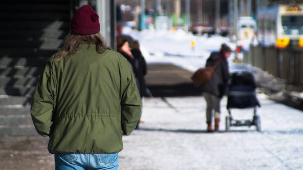 Tuntematon mies kuvattuna selkäpuolelta kävelee eteenpäin kädet taskussa. Taustalla ihmisiä.