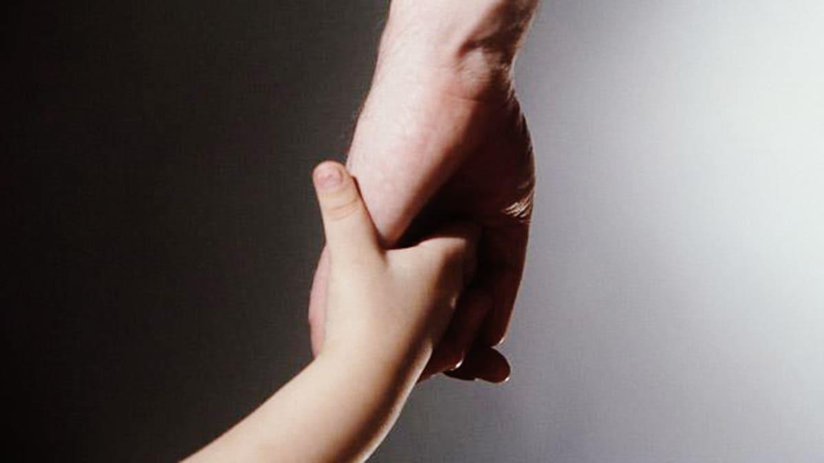 Lapsen käsi aikuisen kädessä.