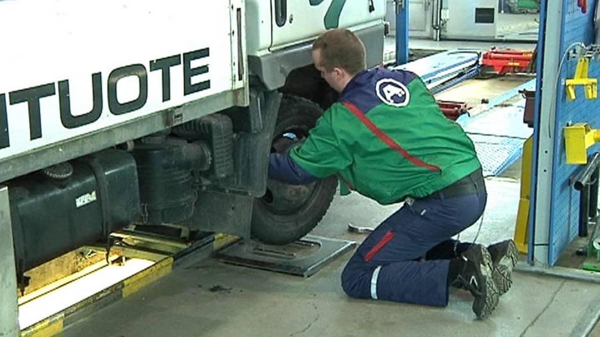 Katsastusmies tutkii kuorma-auton eturipustusta.