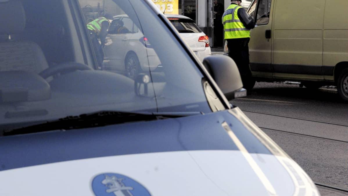 Poliisi sakottaa autoilijoita Helsingin Kampissa.