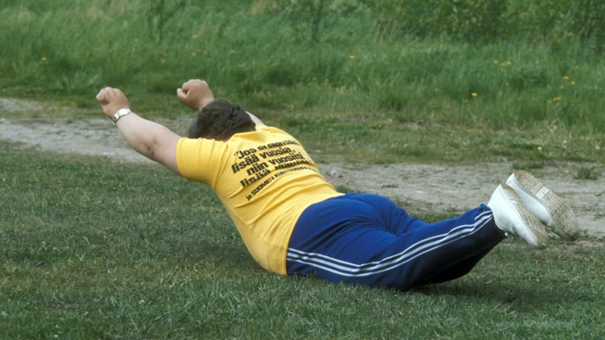 Ylipainoinen mies voimistelee nurmikolla 1970-luvun kuvassa.