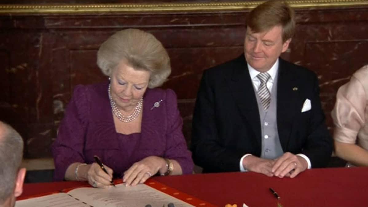 Hollannin kuningatar Beatrix kirjoittaa nimensä kruunustaluopumisasiakirjaan.