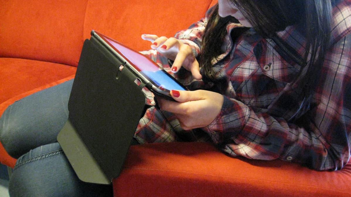 Nuori nainen selailee tablettitietokonetta sohvalla.