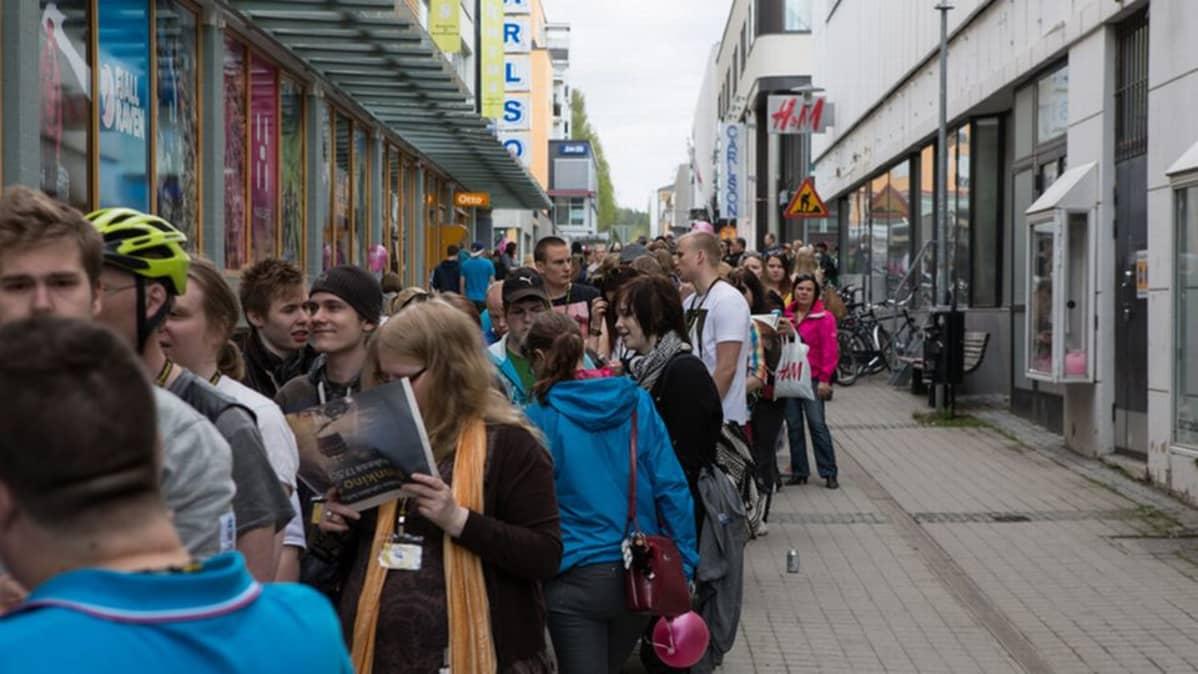 Nuoret jonottavat kadulla.