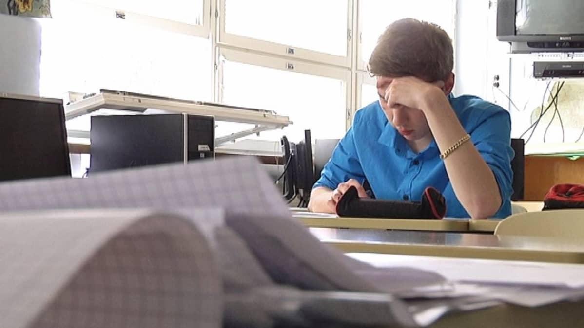 Lukiolaispoika opiskelee istuen pulpetissaan luokkahuoneessa.