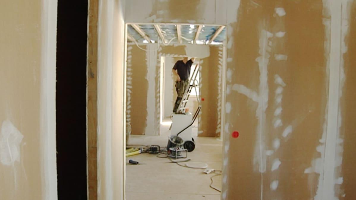 Rakennusmies paklaa seiniä.