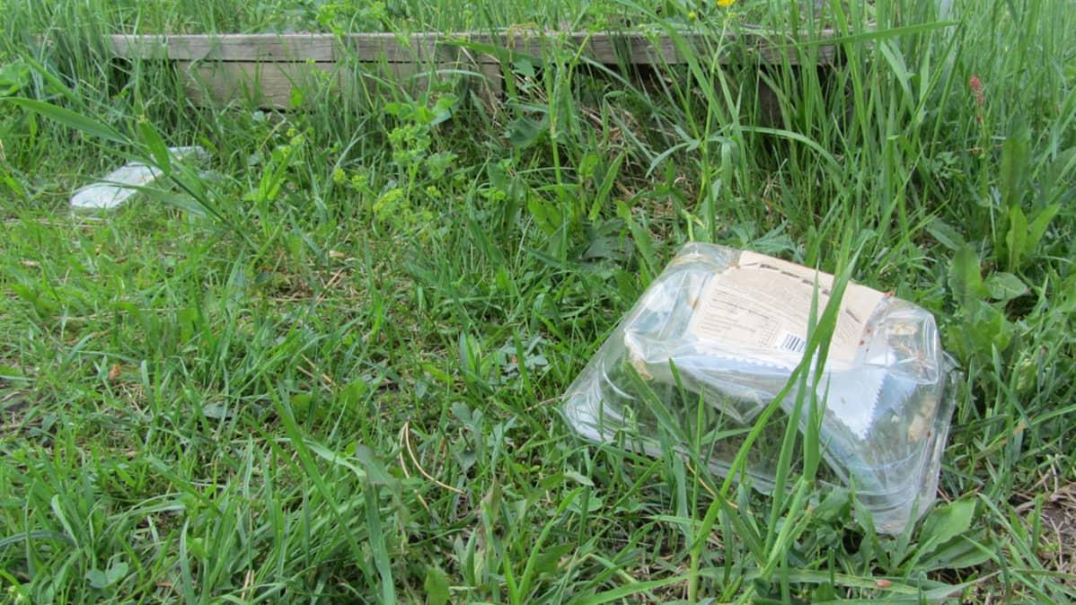 Muovipakkaus nurmikolla.