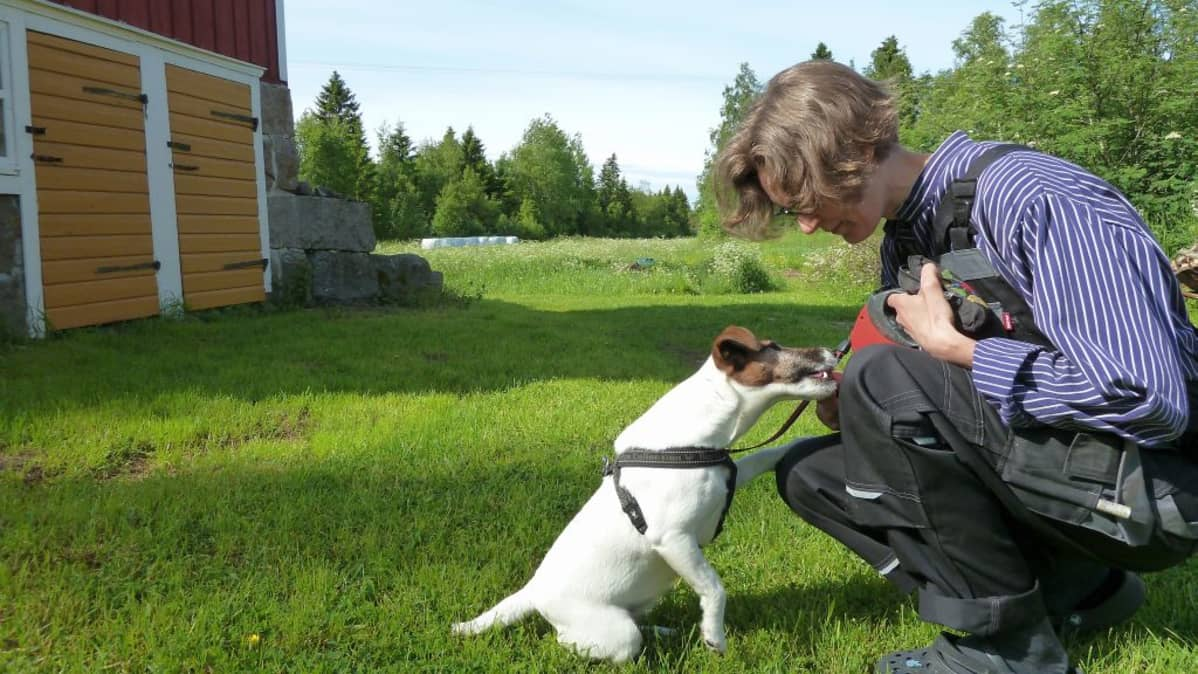 Nainen rapsuttaa koiraa maalaistalon nurkalla Björköbyssä, Mustasaaressa.