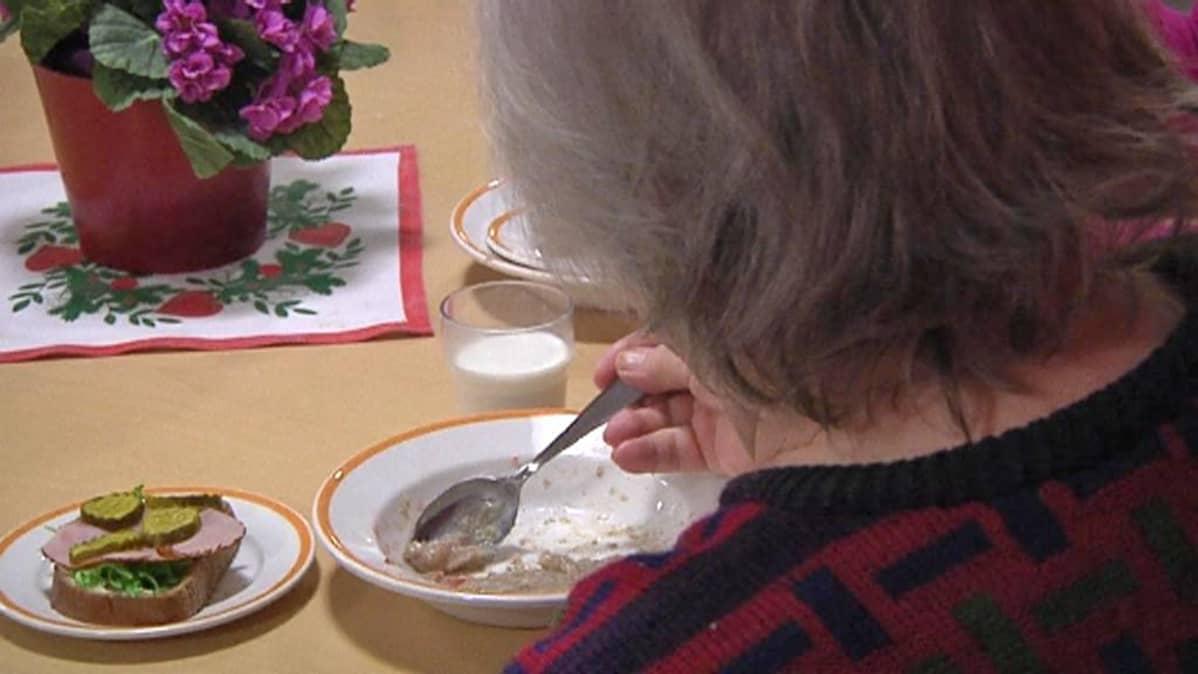 Vanhus syö aamiaista.