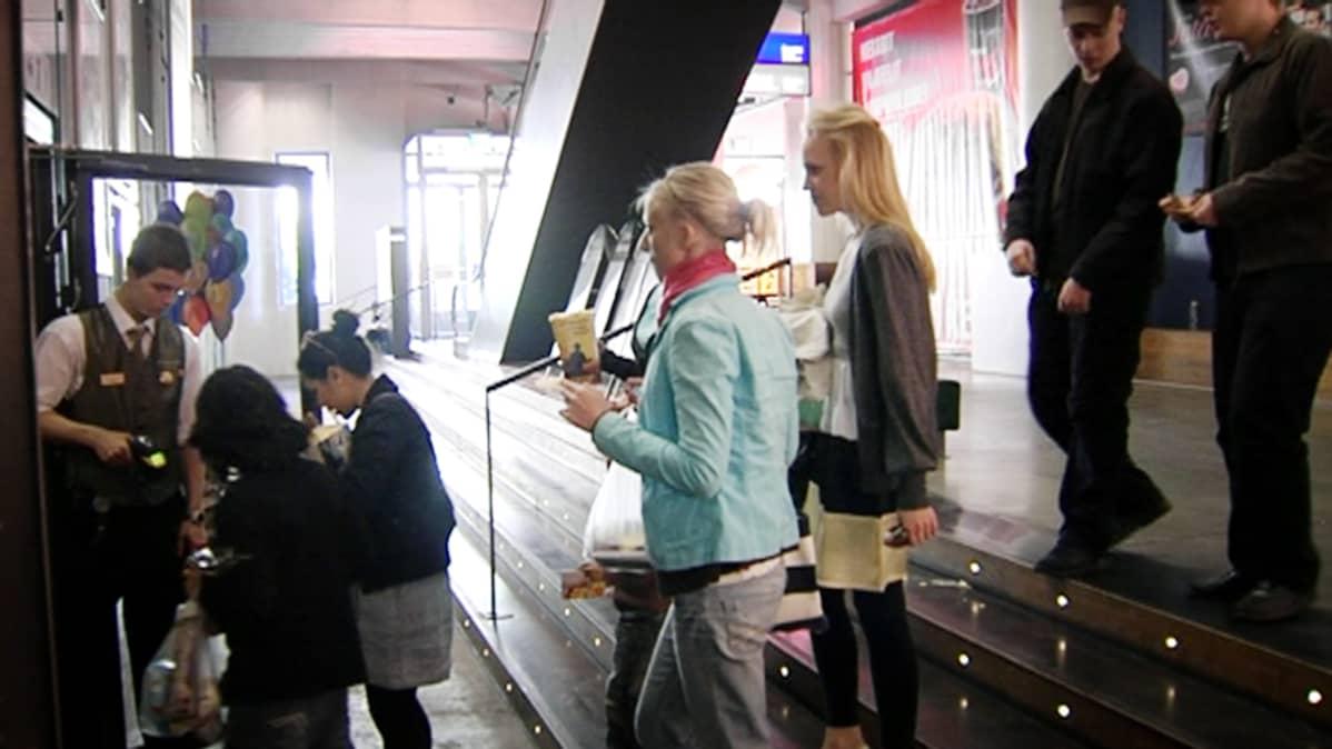 Ihmisiä menossa elokuviin Helsingin Tennispalatsissa.