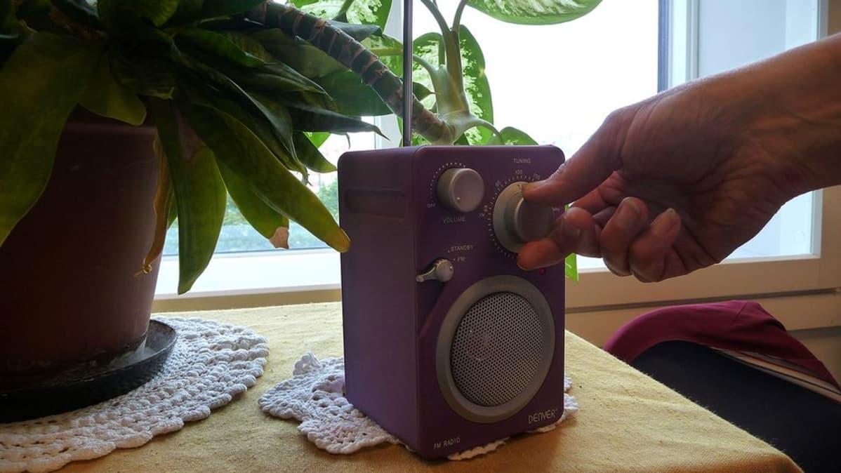 Radio pöydällä ja käsi pyörittämässä oikeaa kanavahakua