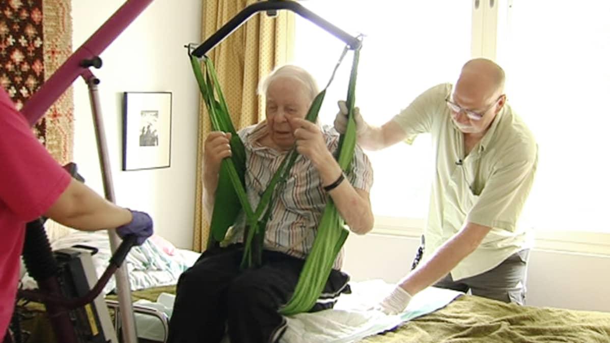 Kotihoitajat auttavat Kalervo Haapasta nousemaan sängystä.