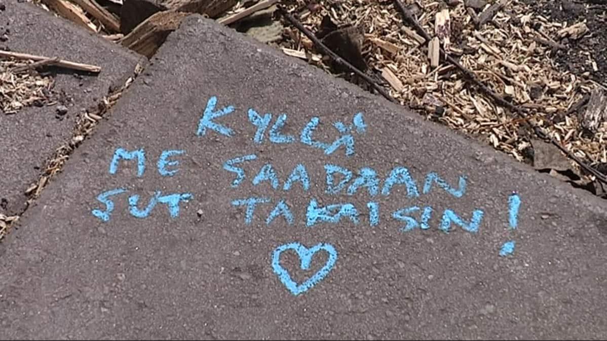Muistokirjoitus kivessä puretun saunan paikalla.