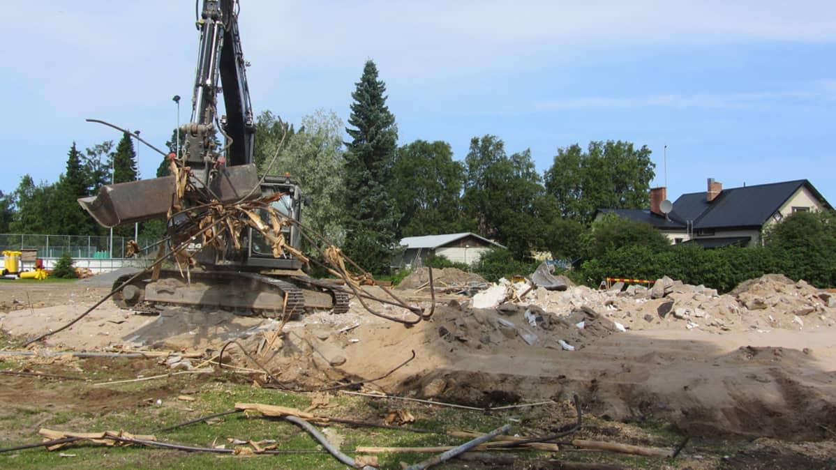 Kuvassa kaivinkone purkaa rakennusta