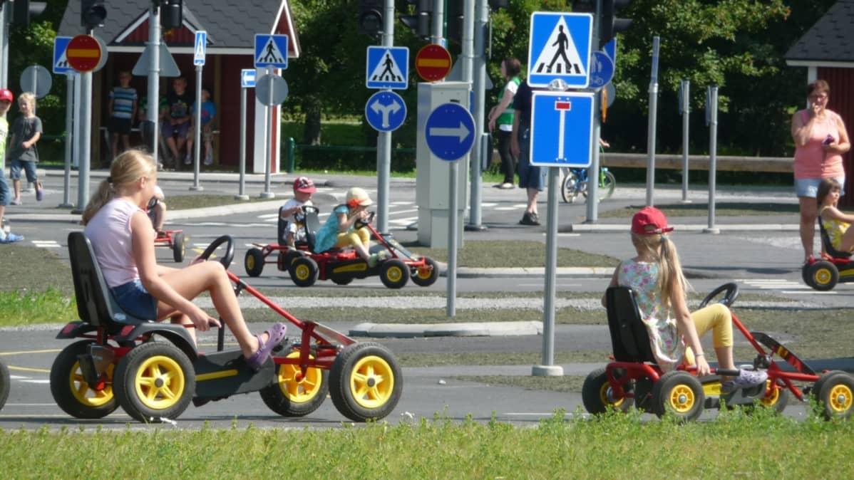 Lapset ajavat polkuautoilla Porin liikennepuistossa.