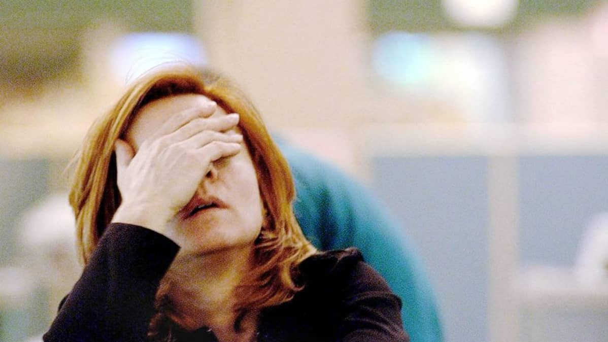 Nainen pitelee kasvoistaan kiinni uupuneena.