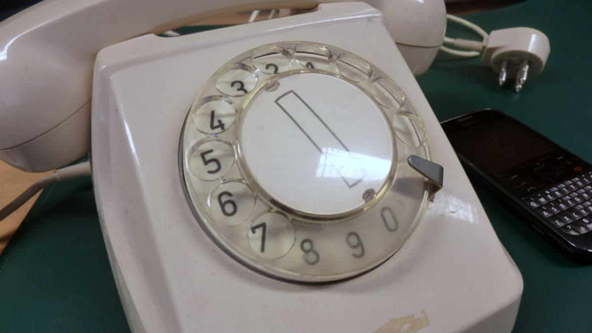 Vanha lankapuhelin ja kännykkä pöydällä.