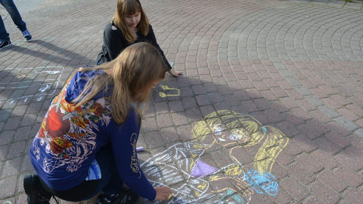 Erityisnuorten partioryhmään kuuluvat kajaanilaiset Katja Pöllänen ja Kiia Määttä taiteilevat liiduilla asfalttiin.