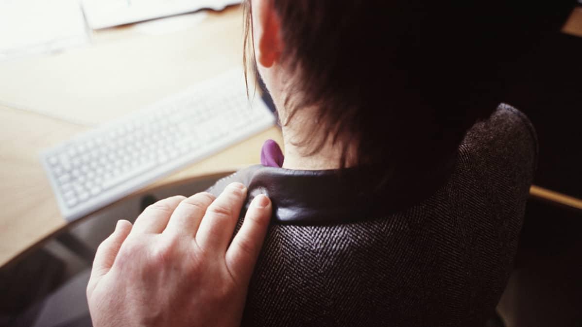 Mies pitää kättään naisen harteilla työpaikalla.