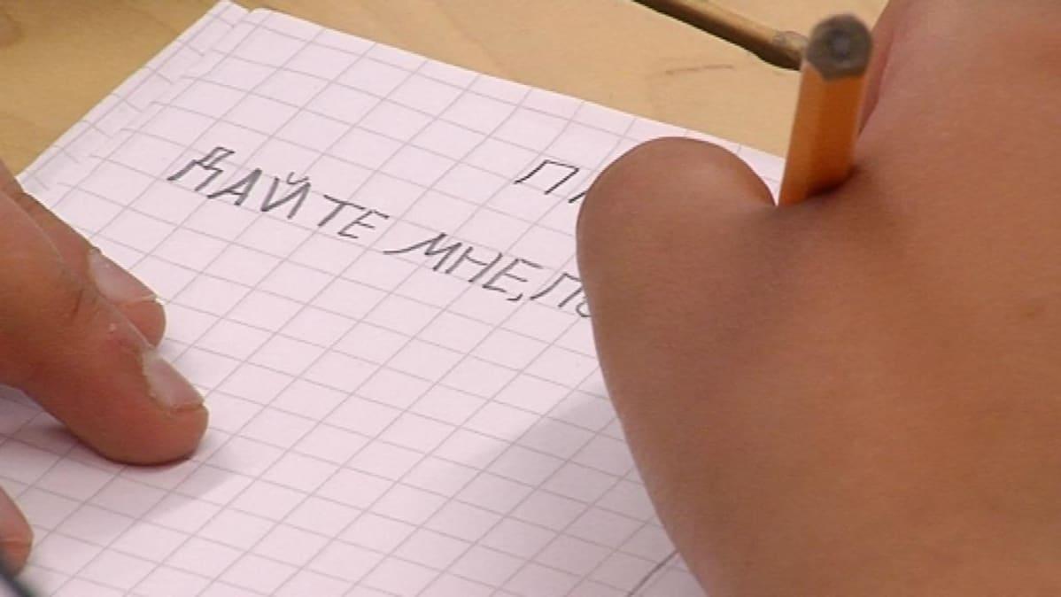 Vihkoon kirjoitetaan kyyrillisiä kirjaimia lyijykynällä