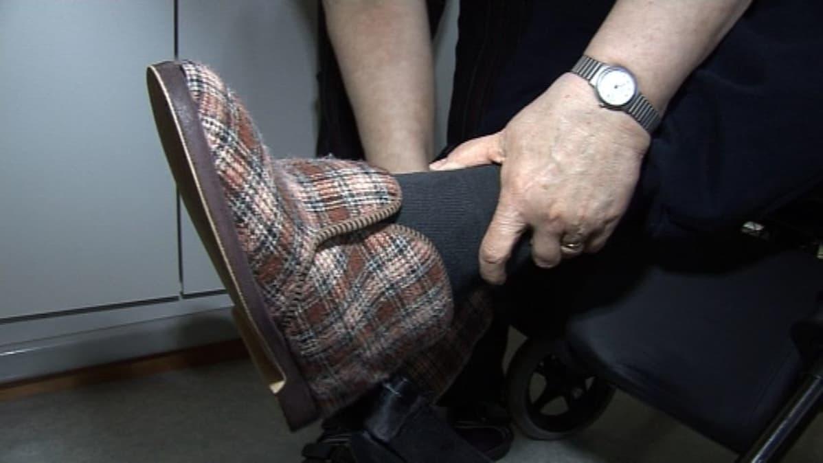 Omaishoitaja laittaa potilaalle kenkää jalkaan.
