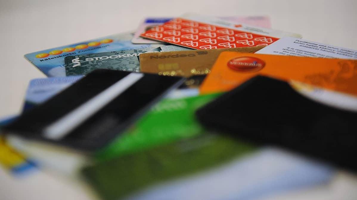 Erilaisia pankki-, etu-, ja jäsenkortteja kasassa.
