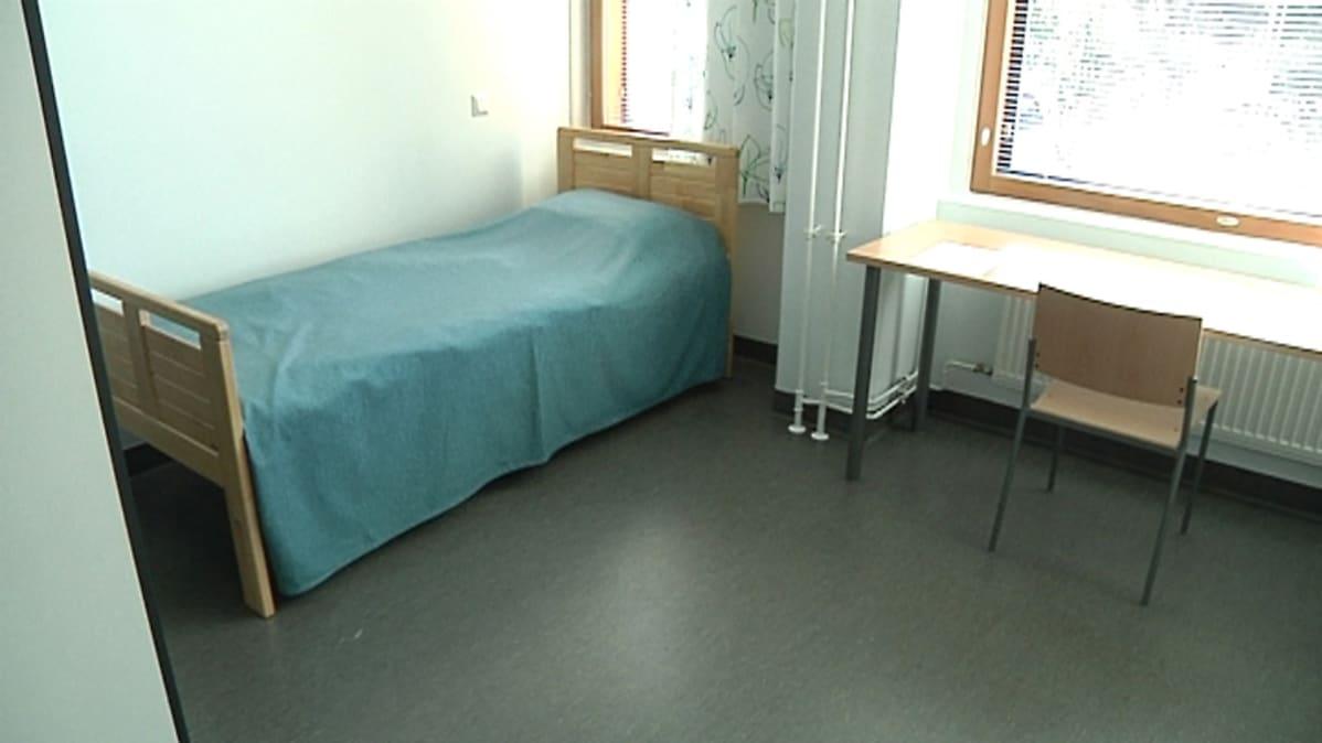 Kuvassa sängyllä, pöydällä ja tuolilla sisustettu asiakashuone