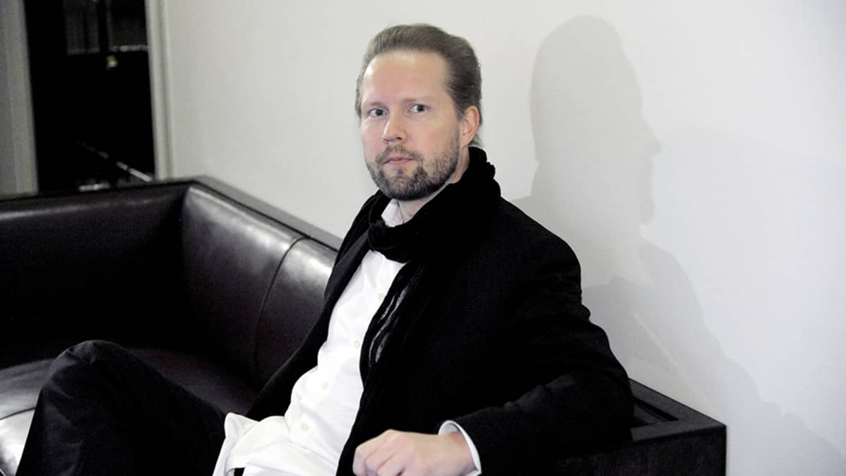 Pekka Himanen odottaa vuoroaan sohvalla istuen eduskunnan käytävällä.