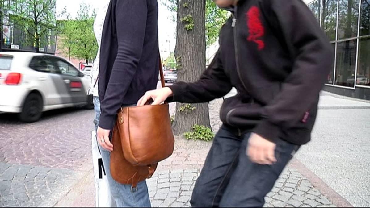 Taskuvaras anastaa lompakon naisen laukusta.