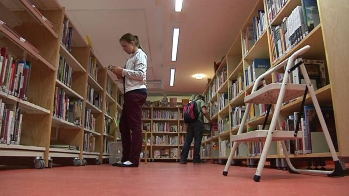 Kaksi nuorta kirjahyllyjen luona.