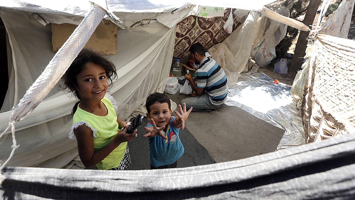 Syyrialainen pakolaisperhe odottamassa väliaikaismajoituksessa pääsyä viralliselle pakolaisleirille.