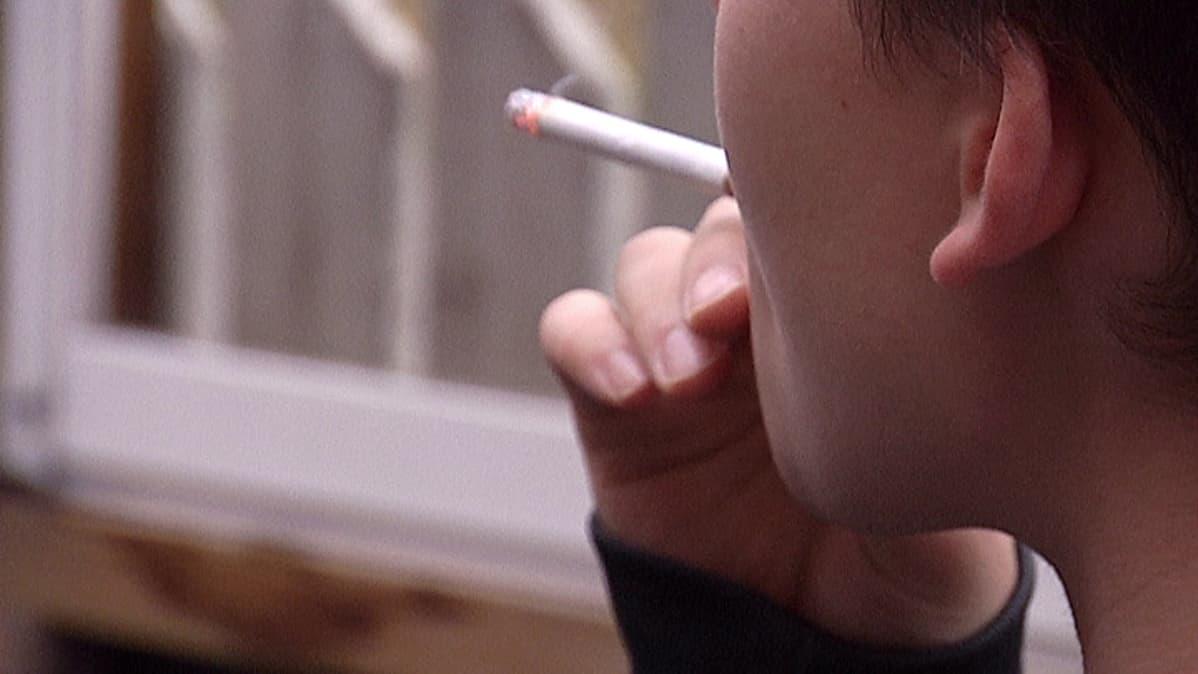 Nuori mies polttaa tupakkaa.