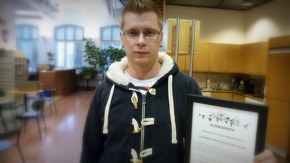 Toni Koski kunniakirja kädessä.