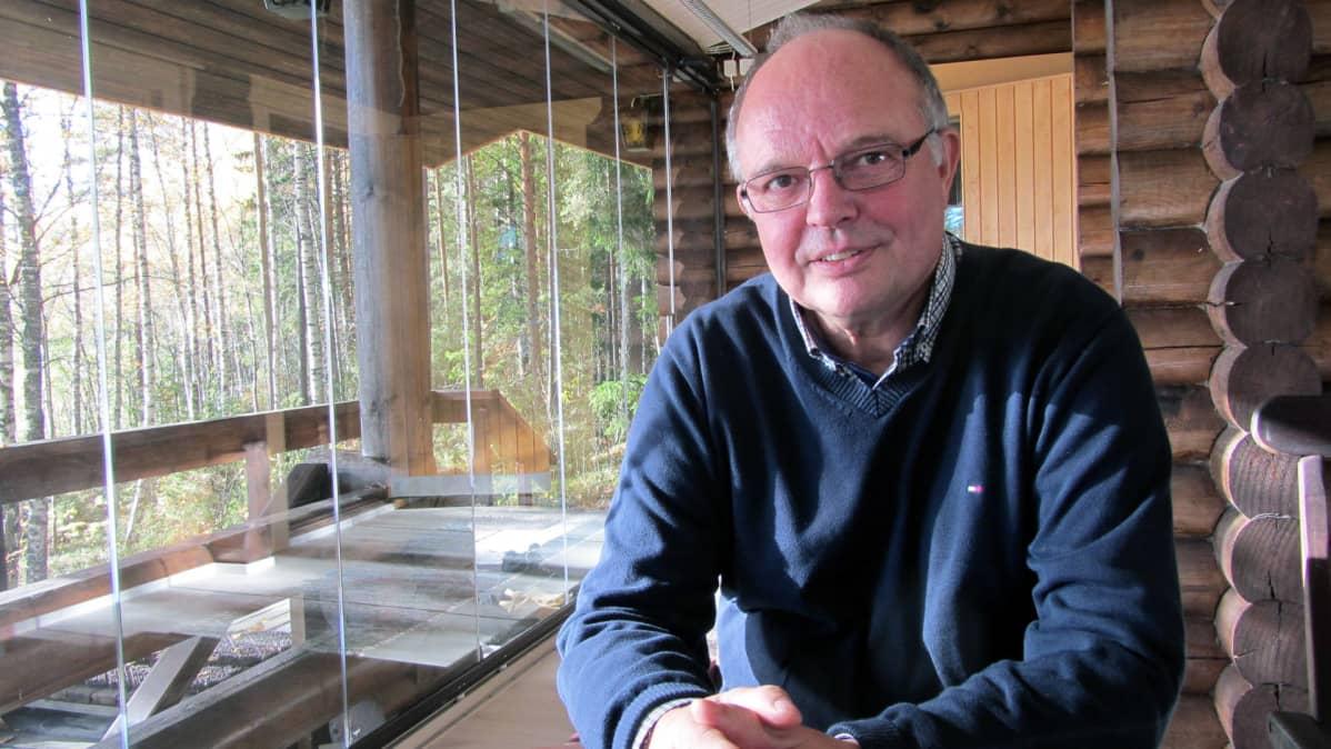 Juhani Putkisto istuu mökkinsä lasitetulla kuistilla.