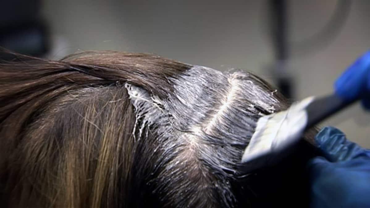 Kampaaja vaalentaa asiakkaansa hiuksia.