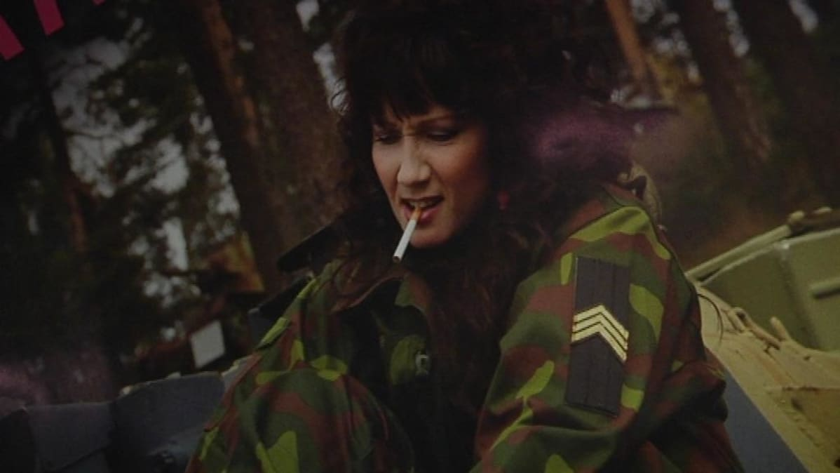 Maastopukuun pukeutunut nainen tupakka suussa