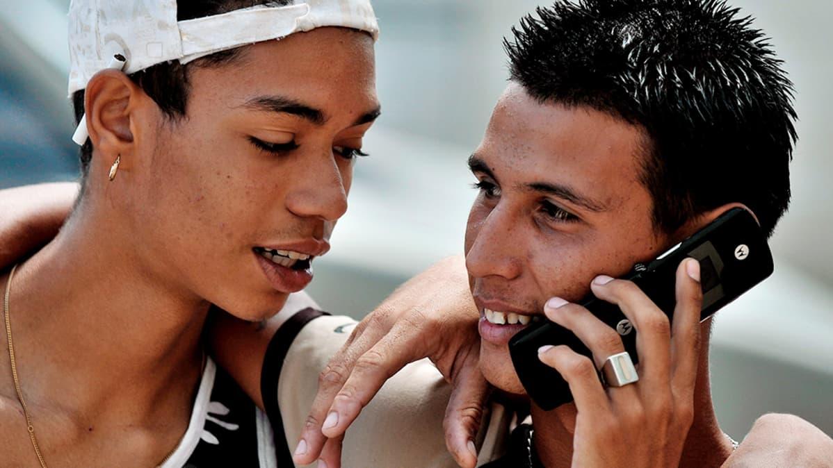 Kuubalaiset nuoret puhuivat matkapuhelimeen Havannassa.