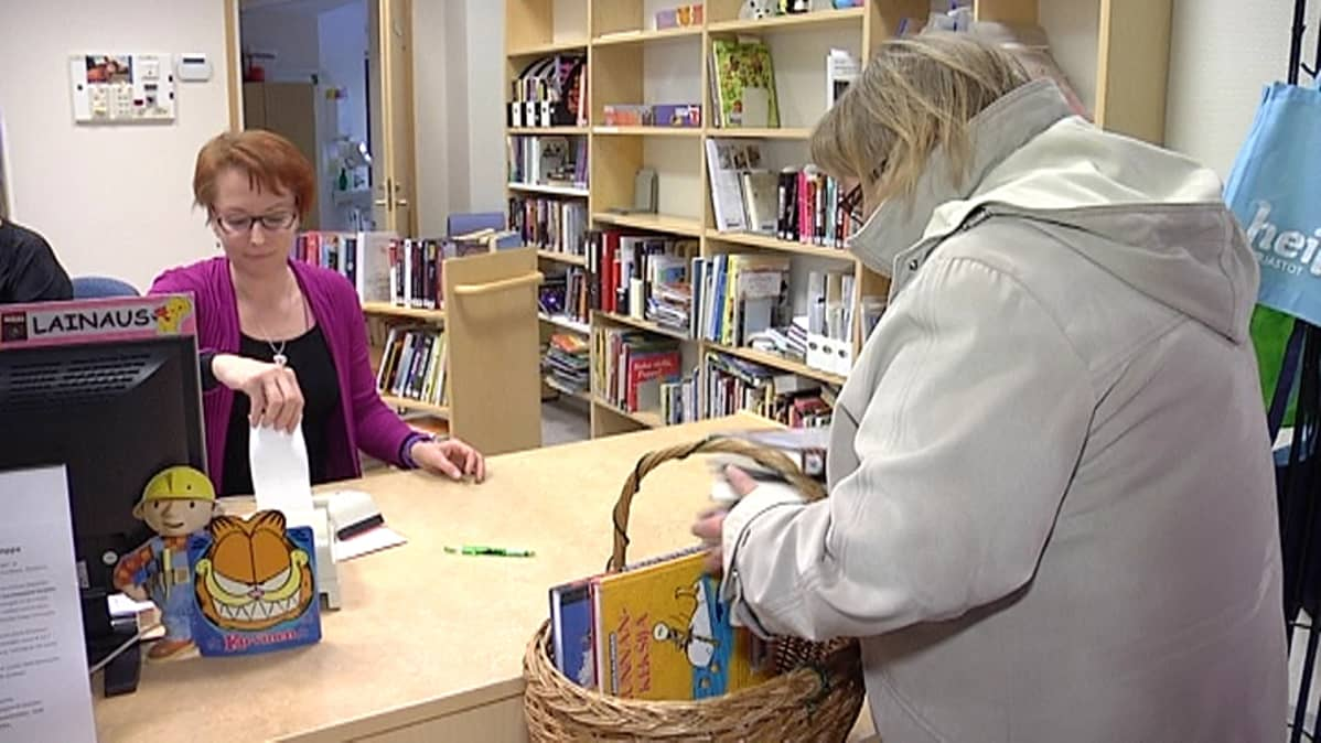 Asiakas lainaamassa kirjoja kirjastossa.