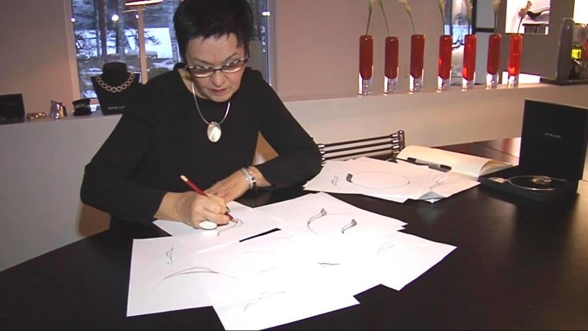 Ritva-Liisa piirtää suunnitelmia