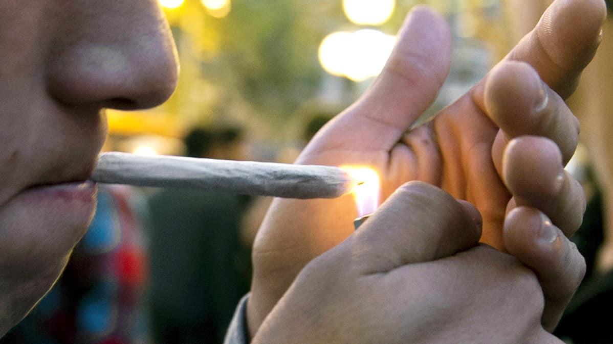 Mies polttaa marihuanasätkää.